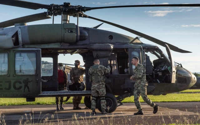 U.S. Army Chief Warrant Officer 3 Mauricio Garcia, left inside Black Hawk door, and his Colombian safety officer counterpart, Capt. Cristian Castiblanco, inspect a refueling operation at Tolemaida Army Base in Colombia. Garcia, a UH-60M Black Hawk pilot and aviation safety officer, is deployed here as part of a technical advising team from U.S. Army Security Assistance Command's Fort Bragg-based training unit, the Security Assistance Training Management Organization. (photo by Richard Bumgardner)