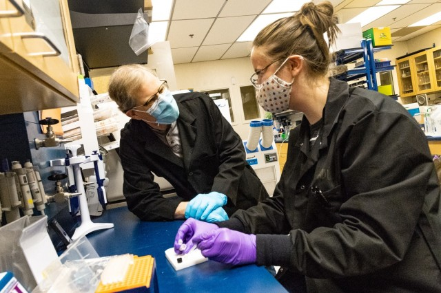 """Army journeyman fellow Meaghan Adler (right) explains a technique used in the laboratory that employs sound waves to """"lyse"""" or break open cells to Dr. Steven James. This is the first step to purifying DNA or proteins inside. Fungal cells are particularly challenging to lyse compared with other microbes."""