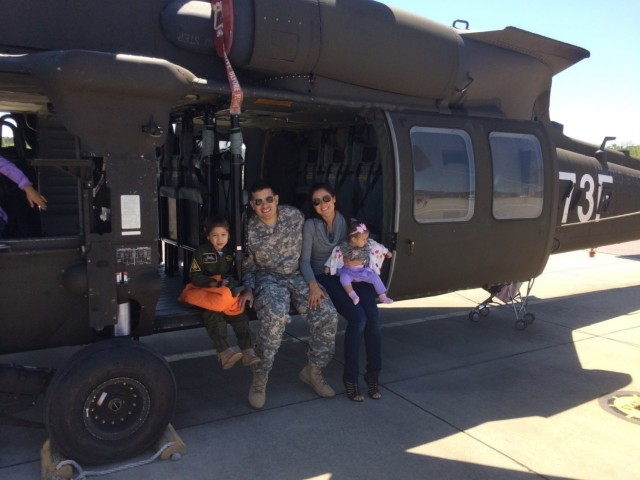 U.S. Army Chief Warrant Officer Mauricio Garcia, a freshly minted UH-60M Black Hawk pilot, poses with his family during Family Day at Lowe Army Airfield, Fort Rucker, Alabama. (Courtesy photo)