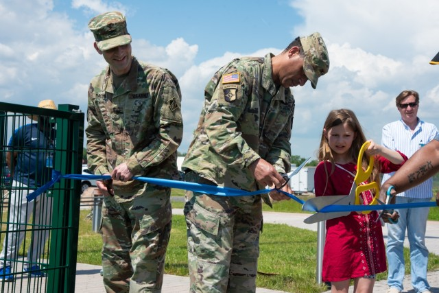 From left to right, U.S. Army Corps of Engineers, Europe District commander Col. Patrick Dagon, U.S. Army Col. Mario A. Washington, Garrison Commander, U.S. Army Garrison (USAG) Wiesbaden, and a family member participate in a ribbon-cutting ceremony for the new artificial turf field located at Clay North in Lucius D. Clay Kaserne, June 4, 2021. The turf field is the latest sports addition for U.S. Army Garrison Wiesbaden and is located next to the Family and Morale Welfare and Recreation Programs (FMWR) Recreation Center at Clay North. (U.S. Army photo by Alfredo Barraza)