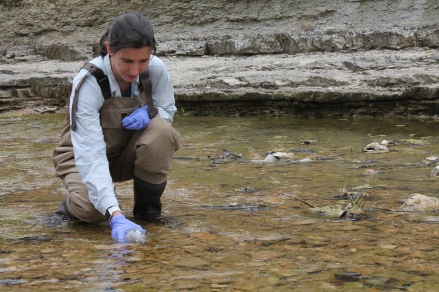 Jinelle Sperry, wildlife biologist with the Construction Engineering Research Laboratory, takes a water sample at Cowhouse Creek at Fort Hood, Texas.