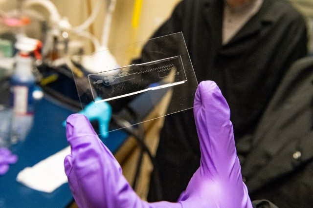Dr. Jose Wippold holds a microfluidic device for generating and mixing droplets to serve as miniature chambers for individual cells.