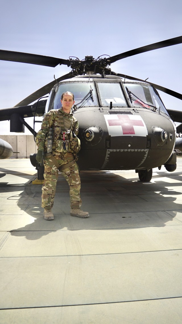 Staff Sgt. Brianna Pritchard, an Army National Guard UH-60 Black Hawk helicopter mechanic from Anchorage, Alaska, poses for a photo in front of a Task Force Phoenix UH-60 Black Hawk MEDEVAC helicopter as Al Asad Air Base, Iraq.