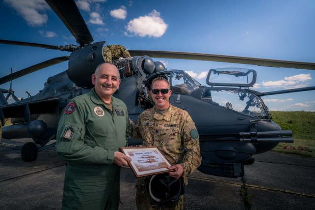 U.S. Army Lt. Col. Matthew Cole, the 1st Battalion, 3rd Aviation Regiment commander, receives a certificate in recognition of his first Mi-24 Hind flight from Hungarian Defense Force Col. Zoltán Rolukó at Szolnok airbase, Hungary, June 3, 2021, during exercise Saber Guardian 21, part of the DEFENDER-Europe 21 series of exercises.