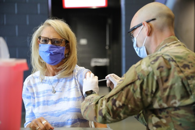 Sherry Melville, an Atlanta native, receives a COVID-19 vaccine from her son, U.S. Army Sgt. Don Melville, a combat medic assigned to 703rd Brigade Support Battalion, 2nd Armored Brigade Combat Team, 3rd Infantry Division, Fort Stewart, Georgia, at the Community Vaccination Center in Atlanta, April 21, 2021. U.S. Northern Command, through U.S. Army North, remains committed to providing continued, flexible Department of Defense support to the Federal Emergency Management Agency as part of the whole-of-government response to COVID-19. (U.S. Army photo by Spc. Daniel Thompson/50th Public Affairs Detachment)