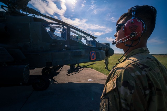 U.S. Army Spc. Yegor Kondratov, an AH-64 crew chief assigned to the 12th Combat Aviation Brigade, Wings of Victory, communicates with his Apache pilot throughout pre-flight checks during attack pilot cross-training with Hungarian Defense Force pilots at Szolnok Air Base, Hungary on June 3, 2021 for exercise Saber Guardian 21, part of the DEFENDER-Europe 21 series of exercises.