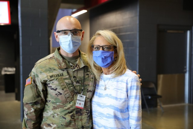 U.S. Army Sgt. Don Melville, a combat medic assigned to 703rd Brigade Support Battalion, 2nd Armored Brigade Combat Team, 3rd Infantry Division, Fort Stewart, Georgia, stands with his mother, Sherry Melville, an Atlanta native, after she received her COVID vaccination from her son at the Community Vaccination Center in Atlanta, April 21, 2021. U.S. Northern Command, through U.S. Army North, remains committed to providing continued, flexible Department of Defense support to the Federal Emergency Management Agency as part of the whole-of-government response to COVID-19. (U.S. Army photo by Spc. Daniel Thompson/50th Public Affairs Detachment)