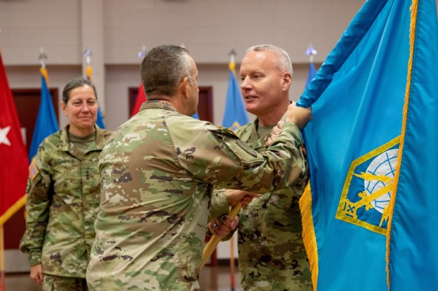 Military Intelligence Readiness Command (MIRC) Commanding General Brig. Gen. Joseph Dziezynski (right) passes the MIRC colors to Command Sgt. Major Brian Bertazon, MIRC senior enlisted leader, during the Military Intelligence Readiness Command's assumption of command ceremony, Fort Belvoir, Virginia, June 5, 2021. (U.S. Army Reserve photo by Maj. Jeku Arce)