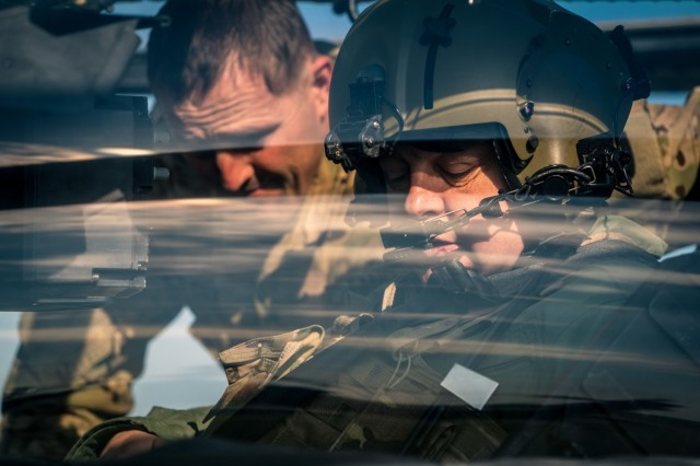 U.S. Army Lt. Col. Matthew Cole, the 1st Battalion, 3rd Aviation Regiment commander, instructs Hungarian Defense Force Brig. Gen. József Koller, the 86th Szolnok Helicopter Base garrison commander on the AH-64 Apache gunner's controls at Szolnok airbase, Hungary, June 3, 2021 during exercise Saber Guardian 21, part of DEFENDER-Europe 21. Cross-training flights like these help to give allies a shared understanding of each other's capabilities and enables interoperability and communication.