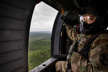 """U.S Army Reserve Cadre observes the terrain below while riding a UH-60 Black Hawk helicopter during the 2021 U.S. Army Reserve Best Warrior/Best Squad Competition at Fort McCoy, Wis., May 25. Approximately 80 Soldiers from across the nation travelled to Fort McCoy to compete in the annually-recurring event running May 19-28. The competition draws the best Soldiers and squads from across the U.S. Army Reserve to earn the title of """"Best Warrior"""" and """"Best Squad"""" among their peers. Competitors are evaluated on their individual and teamwork abilities to adapt and overcome challenging scenarios and battle-focused events, which test their technical and tactical abilities under stress and extreme fatigue."""