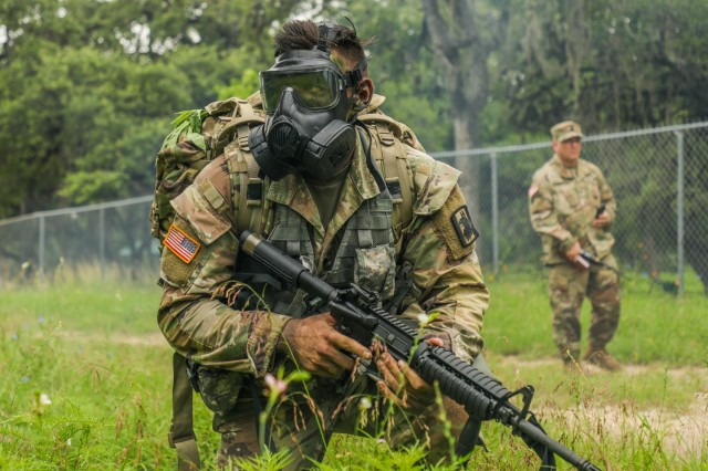 U.S. Army Spc. Justin Earnhart, 470th Military Intelligence Brigade, pulls security while wearing a joint service general purpose mask during an exercise in the Army Futures Command Best Warrior Competition on Fort Sam Houston, Texas, June 9 2021. The Best Warrior Competition evaluates a Soldier's physical ability, tactical performance and knowledge of Army regulations. (U.S. Army photo by Pfc. Joshua Taeckens) (This photo was edited from its original version)