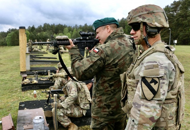Sgt. 1st Class Christopher Wine, assigned to 1st Squadron, 7th U.S. Cavalry Regiment, acts as range safety NCO while a Polish soldier fires an M4 during a marksmanship competition at Forward Operating Site Drawkso Pomorskie Training Area, Poland, May 27, 2021.