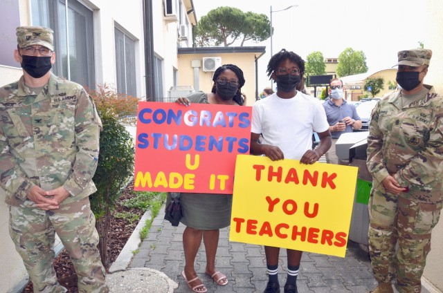 VICENZA, Italy - Soldiers and family members of the Vicenza Military community thank teachers, students and all school staff as they await the exit of the Vicenza High School students on the last day of school June 10, 2021. During the year, all Department of Defense Education Activity Europe schools remained open either in face to face or remote learning. Only five schools, Vicenza Elementary School, Vicenza Middle School, Vicenza High School, Livorno Elementary/Middle School, and Kleine Brogel Elementary School in Belgium remained open to in person instruction the entire school year.