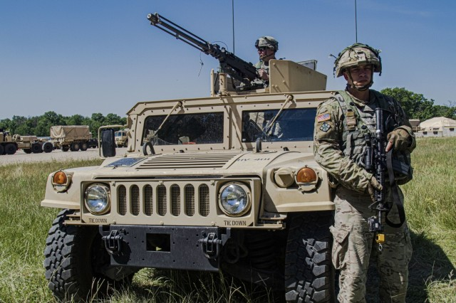 Spc. Kevin Dempsey (left) and  Spc. Andrew Hogan, of the 702nd Engineer Company, stand guard at the vehicle entrance of tactical training base Justice as a part of Warrior Exercise 86-21-02 at Fort McCoy, Wis., June 9, 2021.   WAREX is an annual training event integrating both combat support and combat service support assets to train United States Army Reserve Soldiers. The exercise facilitates opportunities to proactively handle real-world scenarios with competency in infantry tactics, defensive posture, vertical and horizontal construction, convoy operations and maintenance, communication planning and security, and media operations. (U.S. Army Reserve photo by Sgt. Michael Ito, 364th TPASE)