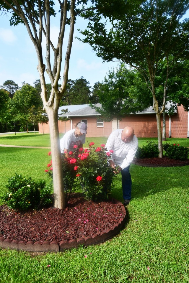 Vickey Stevenson, horticultural attendant (left) and James Armes III, Central Louisiana Veterans Cemetery director, inspect a rose bush and shrubs to make sure they don't need pruning or fertilizer, as well as the landscaping for weeds that need to be removed.