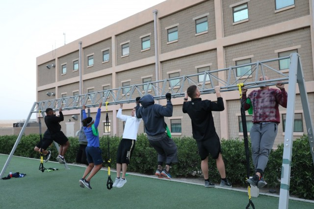 Maj. Anthony Sims-Hall, 1st Theater Sustainment Command, theater mortuary affairs officer, leads a functional fitness workout for Soldiers at Camp Arifjan, Kuwait. Maj. Sims-Hall takes personal passion and hobbies and turns them into resiliency opportunities for Soldiers while deployed. (U.S. Army photo by Capt. Elizabeth Rogers)