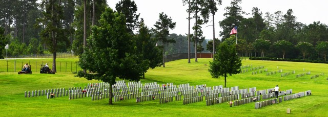 Horticultural staff Junior Condon (left) and Marshall Evans mow the lawn at the Central Louisiana Veterans Cemetery as Vickey Stevenson removes old arrangements on the grave sites June 7.