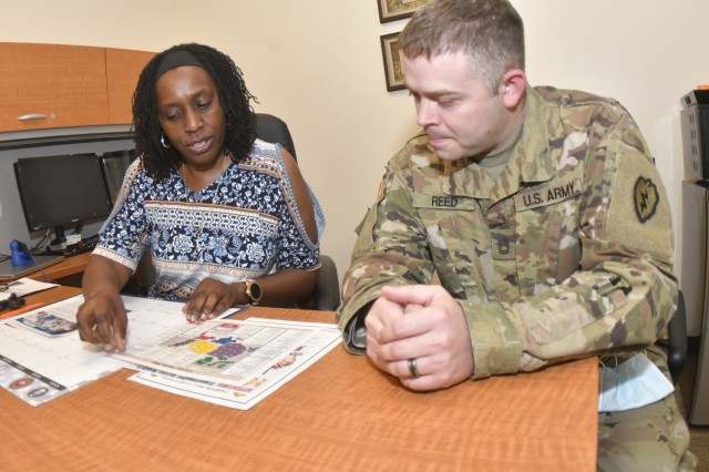 Verna Bellamy, transition services specialist, Transition Assistance Program, reviews information with Sgt. 1st Class Peter Reed, Headquarters and Headquarters Company, 244th Quartermaster Battalion.