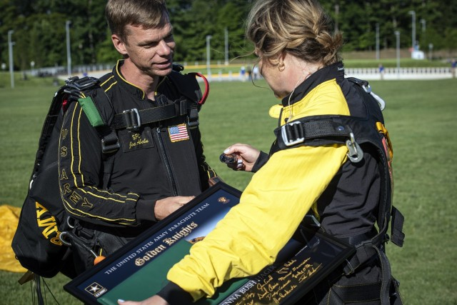 """Sgt. 1st Class Joseph Abeln, the Army Golden Knights tandem team leader, presents a coin to Jenna Bush-Hager, the daughter and granddaughter of two former presidents and """"Today"""" show co-host, after they completed a tandem jump from 10,000 feet to honor the memory of President George H. W. Bush June 17, 2021."""
