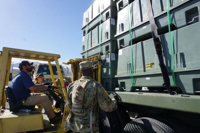 Forklift and operator place material on truck bed as soldiers strap down load