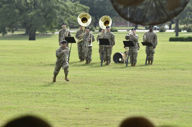 U.S. Army Capt. Nema B. Nematpour sprints across the parade field as the 41st Army Band plays adjutants call during the 1st Aviation Brigade change of command ceremony at Fort Rucker, Alabama, June 18, 2021. (U.S. Army photo by Lt. Col. Andy Thaggard)