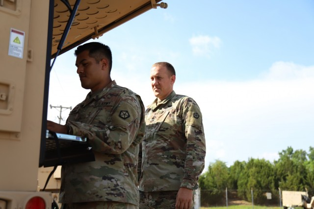 Two V Corps Soldiers work on communications systems during the DEFENDER-Europe 21 command post exercise, June 10, 2021, on Fort Knox, Kentucky. The communications systems were worked around the clock and through some unfavorable weather conditions  to keep operational awareness and ensure the mission would be a success during the CPX .