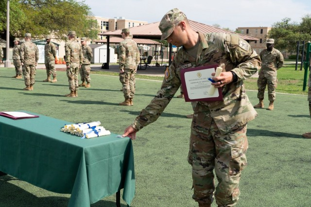 The 68P Radiology Class 20-005 Army Honor Graduate receives a coin from the 68P service lead using social distance and other COVID-19 mitigation measures during a closed graduation on Joint Base San Antonio- Fort Sam Houston, April 2020.  On Monday, June 28, 2021, the U.S. Army Medical Center of Excellence will conduct a pilot graduation for 14 68P Army Soldiers before making the final decision on full implementation of policies and procedures allowing open graduations.