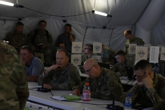 The commanding general of V Corps,  Lt. Gen. John Kolasheski (left center), and the deputy commanding general support, Maj. Gen. Robert Burke (right center), receive a virtual brief during the Defender Europe 21 command post exercise, June 3, 2021, on Fort Knox, Kentucky. The CPX was another step in the Victory Corps march to full operational capability and becoming a certified warfighting headquarters.
