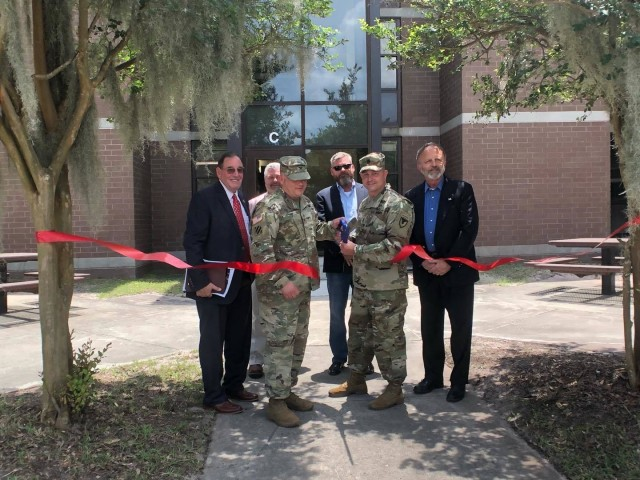 Acting Assistant Secretary of the Army (Installations, Environment & Energy), Mr. Jack Surash (Left), along with members of the Fort Stewart-Hunter Army Airfield Garrison command team and DPW leadership, participate in a ribbon cutting ceremony at the newly renovated 1st Armored Brigade Combat Team's barracks complex, which were renovated prior to the unit's redeployment.