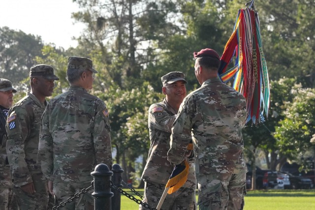 U.S. Army Maj. Gen. Antonio A. Aguto, outgoing commander of the 3rd Infantry Division, passes the Division colors to Lt. Gen. Michael Kurilla, commanding general of the XVII Airborne Corps, symbolizing the relinquishment of command during a Change of Command Ceremony, June 21, 2021. Aguto led the Division through Hurricane Dorian impacts, the global COVID-19 pandemic and multiple subordinate units' deployments to U.S. Central Command area of responsibility, Europe, and Pacific. (U.S. Army Photo by Pfc. Caitlin Wilkins, 50th Public Affairs Detachment)