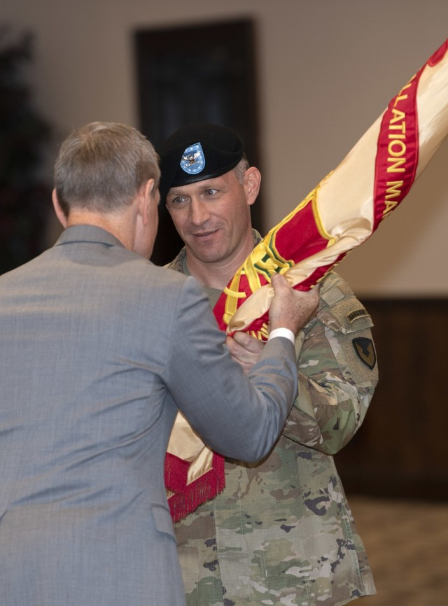 Col. Ryan Hanson, garrison commander, takes the unit colors from Mr. Vincent Grewatz, director of Installation Management Command's Directorate of Training, during a change of command ceremony June 15 at Victory Hall on post. Hanson took the reins of the unit from Col. John ' Wes' Hankins.