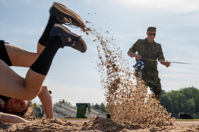 A Soldier crashes into the sand pit after attempting the long jump event during a German Sports Badge event on Panzer Kaserne, Germany, June 19, 2021.
