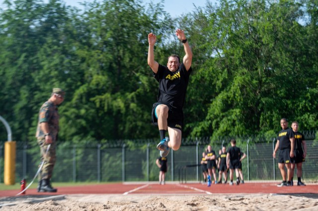 Capt. Jonathan Kuhlman, a JAG with the 21st Theater Sustainment Command, attempts a long jump during a German Sports Badge event on Panzer Kaserne, Germany, June 19, 2021.