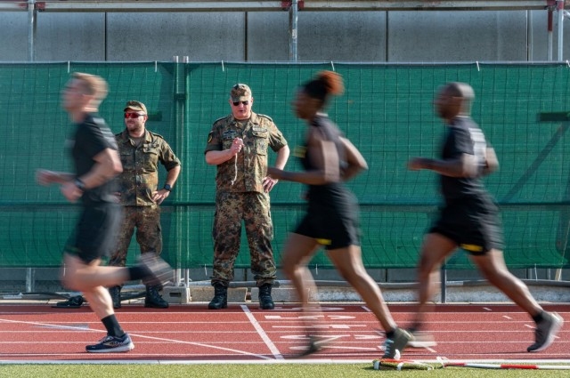 American Soldiers run past German Soldiers who are timing a 3-5 KM run during a German Sports Badge event on Panzer Kaserne, Germany, June 19, 2021.