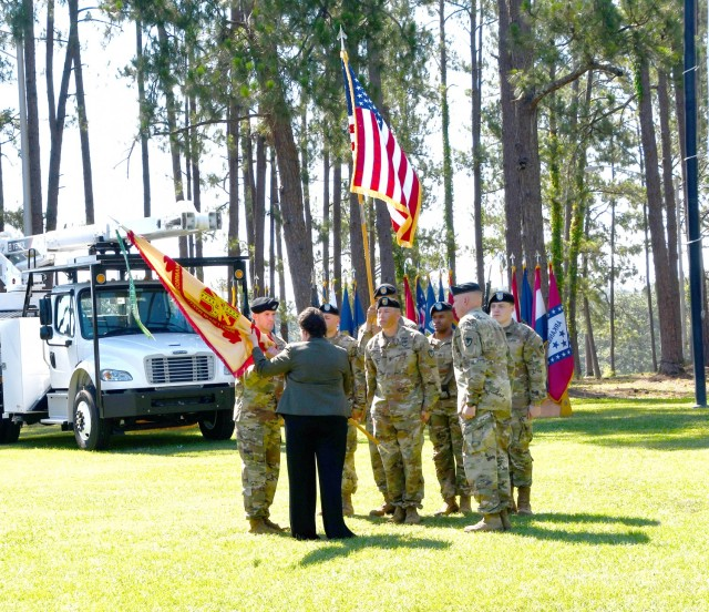 Brenda McCullough, director, IMCOM-Readiness, passes the Fort Polk Garrison colors to Col. Sam Smith, incoming garrison commander, during a change of command ceremony June 18 at Fort Polk's Warrior Field, as outgoing commander, Col. Ryan K. Roseberry looks on.