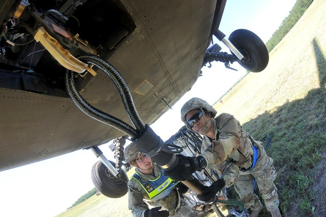 Pvt. NyKaya McLemore, with the help of her instructor, Staff Sgt. George Avery, uses the reach pendant to connect cargo to the underside of a 6-ton, hovering Black Hawk helicopter during sling load operations June 17 at McLaney Drop Zone.