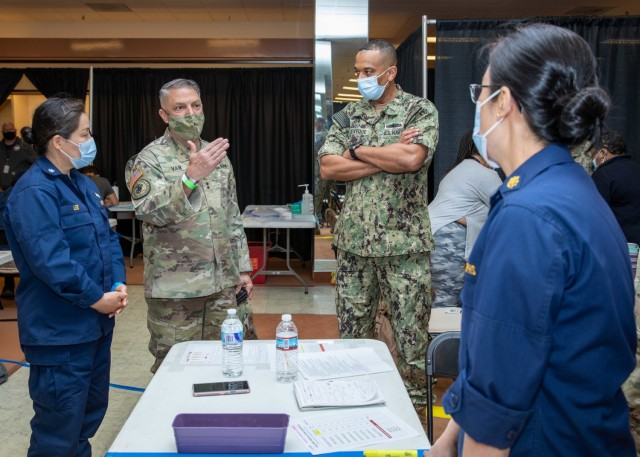 Joint Task Force Civil Support Commanding General U.S. Army Maj. Gen. Jeff Van, middle, speaks with U.S. Public Health Service Lt. Cmdr. Jina Kwak, a pharmacist, right, during a tour of the state-run, federally-supported COVID-19 community vaccination center in Norfolk, Virginia, April 3, 2021. U.S. Northern Command, through U.S. Army North, remains committed to providing continued, flexible Department of Defense support to the Federal Emergency Management Agency as part of the whole- of-government response to COVID 19. (U.S. Navy photo by Mass Communication Specialist 2nd Class Michael H. Lehman)