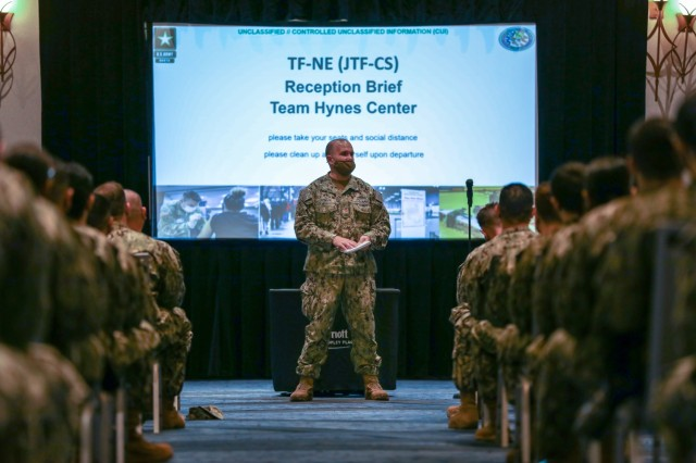 Lt. Cmdr. Aaron Piontek, assigned to Navy Cargo Handling Battalion ONE, Williamsburg, Virginia, briefs U.S. service members during in-processing March 27, 2021, Boston. U.S. service members from across the country are deployed in support of the Department of Defense federal vaccine response operations. U.S. Northern Command, through U.S. Army North, remains committed to providing continued, flexible DoD support to the Federal Emergency Management Agency as part of the whole-of-government response to COVID-19. (U.S. Army photo by Spc. Kelsey Simmons / 14th Public Affairs Detachment)