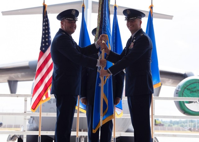 U.S. Air Force Maj. Gen. Kenneth T. Bibb Jr., 18th Air Force commander, presents Col. David A. Fazenbaker, 62nd Airlift Wing commander, with the 62nd AW's guidon during a change of command ceremony at Joint Base Lewis-McChord, Washington, June 15, 2021. Prior to taking command of the 62nd AW, Fazenbaker was the 14th Flying Training Wing vice commander at Columbus Air Force Base, Mississippi. (U.S. Air Force photo by Senior Airman Zoe Thacker)