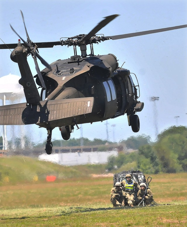 A UH-60 Black Hawk helicopter descends toward an instructor, ammunition specialist students and simulated cargo to perform a sling load operation June 17 at McLaney Drop Zone. The training event is part of the eight-week 89B Ammunition Specialist Course offered by the Ordnance School, an element of the U.S. Army Combined Arms Support Command.