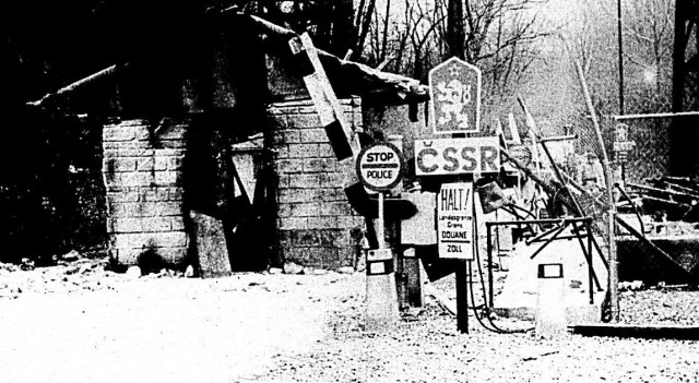 """A battered guardhouse stands in the middle of the road after being blown off its foundation by a customized motor coach. The checkpoint, part of the """"Stripes"""" set, stood on the """"Czechoslovakian"""" border before its celluloid demise. Columbia Pictures movie makers decided that a site on old Wilson Road, under the Illinois Central Gulf railroad trestle, would be perfect for the role of the communist country."""