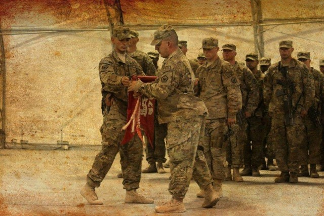 Maj. Donald A. Schmidt, left, the executive officer of the 9th Brigade Engineer Battalion, 2nd Armored Brigade Combat Team, 3rd Infantry Division, conducts the uncasing ceremony of the 576th Engineer Company, 4th Engineer Battalion, 36th Engineer Brigade, as the company commander at Shindand Air Base, Afghanistan, August 2013. The Army is proud of its lesbian, gay, bisexual, transgender or questioning Soldiers who serve with distinction and are role models for exemplifying the Army's highest values. (Courtesy Photo)