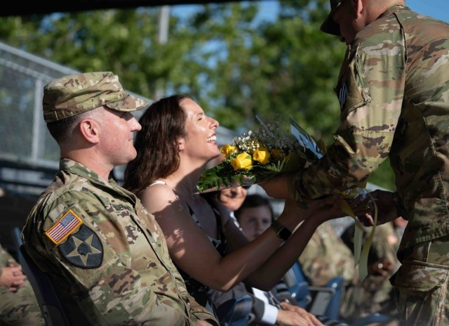 Mrs. Christy Hodermarsky, middle, the spouse of Lt. Col. Daniel G. Hodermarsky, left, the incoming commander of the 3rd Battalion, 67th armored Regiment, 2nd Armored Brigade Combat Team, 3rd Infantry Division, receives a bouquet of yellow roses as the a symbolic welcome gesture from the unit during a change of command ceremony on Cottrell Field at Fort Stewart, Georgia, June 16, 2021. (U.S Army Photo by Spc. Devron Bost)