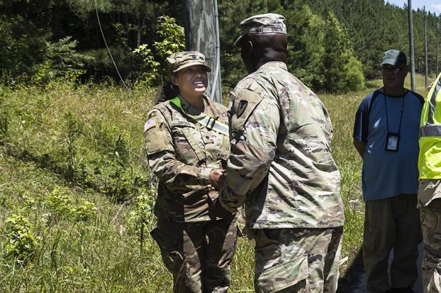 Lt. Col Thomas Smith, Anniston Munitions Center commander, presents a Commander's Coin for Excellence to a Solider from the Alabama Army National Guard's 781st Transportation Company.