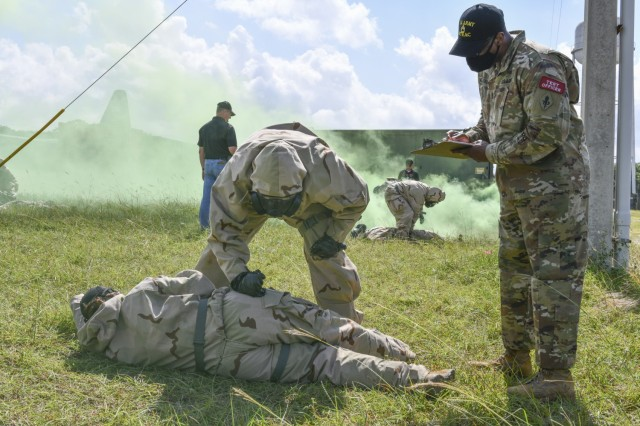 Sgt. 1st Class Elijah Williamson, USAMTEAC Test Officer, takes notes as a test player practice administering the ROCS auto-injector on a simulated casualty.