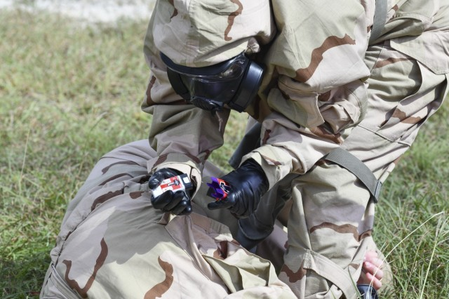 While wearing MOPP Level 4 gear a test player prepares to use a ROCS auto-injector on a simulated causality.