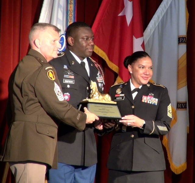 Command Sgt. Maj. Warren Robinson and (right) Sgt. Major Julie Guerra presents Staff Sgt. Marcus Simpson, the 2021 Command Sgt. Maj. Doug Russell Award for Excellence in Military Intelligence during the 2020-2021 Military Intelligence Hall of Fame Luncheon Ceremony at Fort Huachuca, Ariz.