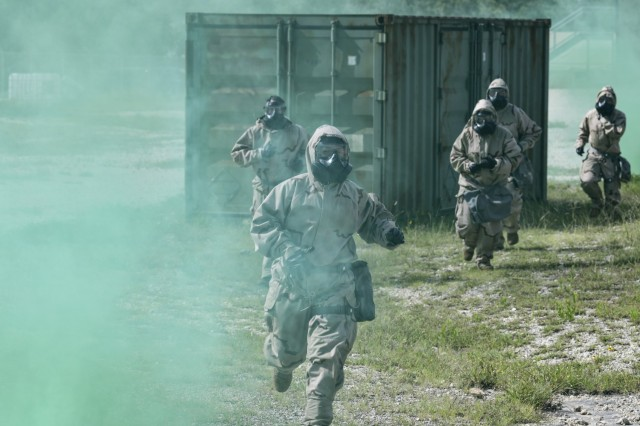 Test players wearing Level 4 MOPP gear advance to treat simulated casualties at Camp Bullis, TX.