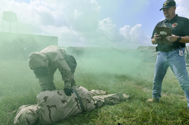 USAMTEAC Test Officer Charles Lohsandt looks on as test players wearing MOPP Level 4 protective gear test the functionality and usability of the ROCS auto-injector within the operational environment.