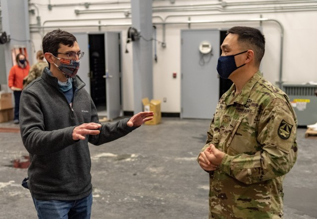 Army researcher Eric Spero (left) discusses robotics with Soldiers.